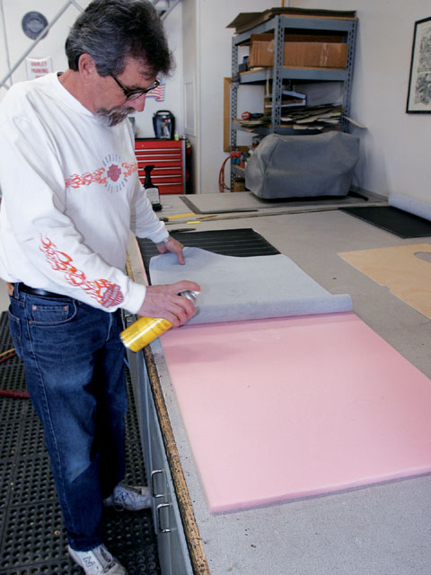 Sid begins the process of making a pleated panel. He sprays light adhesive onto scrim-backed foam.