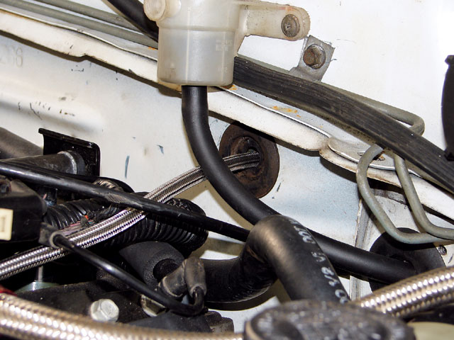 The supplied 4AN feed line is laid along the driver side of the LS1's intake manifold, and feeds from the interior through the original speedometer cable's firewall grommet.