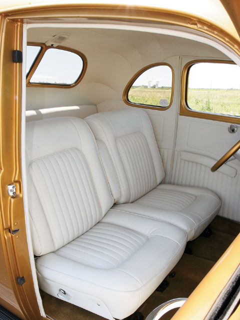 A pair of buckets from a fullsize Ford from the '70s was the base from which to work when it came to the interior of Doug's coupe. The white tuck 'n' roll, headliner, and door panels made by Red's Upholstery are a stark contrast to the gold '40 dash, steering column, and steering wheel.