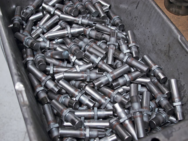 Every bolt, nut, and stud starts life like this, on a giant coil of steel. The wire is cut, the head formed, threads cut, end faced, and numerous other processes performed to turn this into a mountain of bolts.