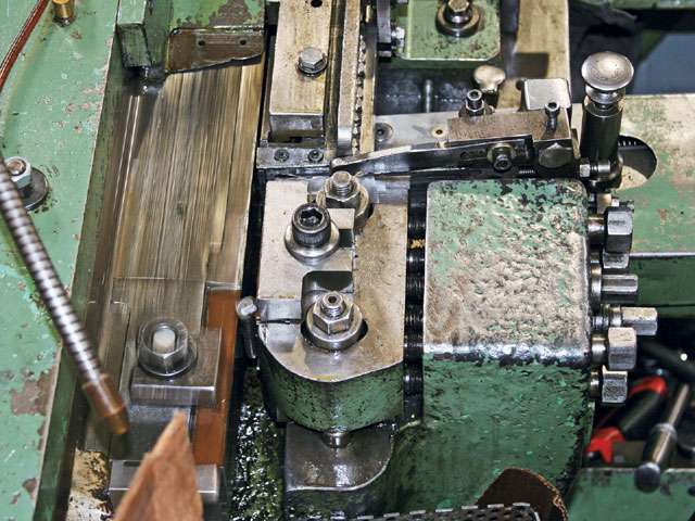 Look closely to see the threads being formed (arrow) on this rolling machine, one of several types.
