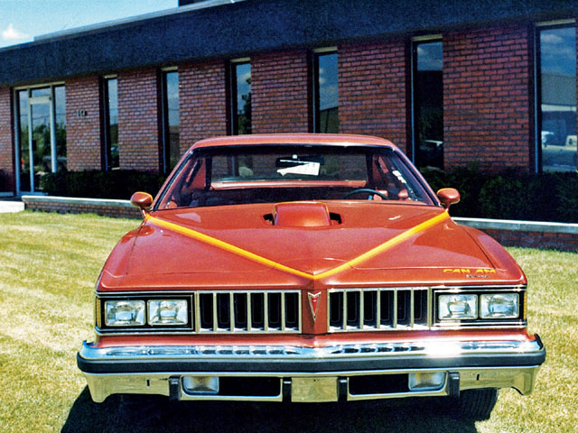 Parked in front of the Motortown facility, this is Jim Wangers' original Carousel Red 1977 LeMans Judge proposal rejected by Pontiac management. The car was later fitted with the Can Am emblems.