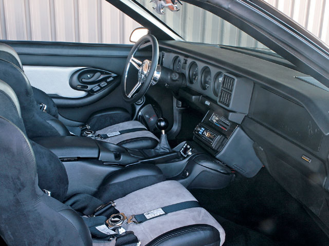 The interior features a blend of Third- and Fourth-Gen T/A pieces, including a '91 T/A dash and gauges, '96 T/A console, and custom door panels made from Third- and Fourth-Gen door panel parts built by Kim's Trim, of Cynthiana, Kentucky. Other interior mods include Corbeau micro-suede seats, 5-point harnesses, Budnik Beveled Sport steering wheel, Pro 5.0 shifter, and an Alpine stereo component system featuring an Alpine head unit, 40wx4 amp, and eight speakers.