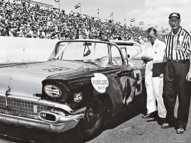Cotton Owens takes a moment from racing his '58 Pontiac Chieftain at Darlington as NASCAR inspector William (Bill) Taylor looks on.