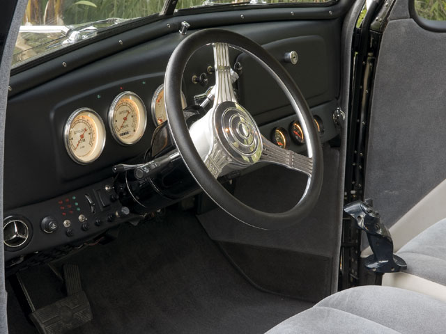 The stock dash has a trio of Classic instruments; the added panel below has a variety of switches, indicator lights, and auto Meter gauges. note the joystick between the seats.