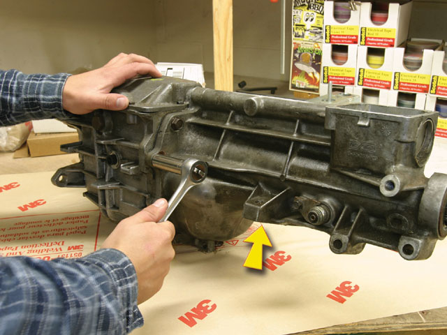 The first step in the swap is to remove the old Camaro tailshaft. Start by shifting the transmission into neutral before removing the shift lever and assembly from the tailshaft. Next, the offset lever roll pin must be driven out to free the shifter shaft.