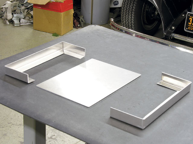 The fundamental elements of the battery box include the floor and the frame. The frame is little more than two strips of 14-gauge aluminum sheet, brake-bent 90 degrees.