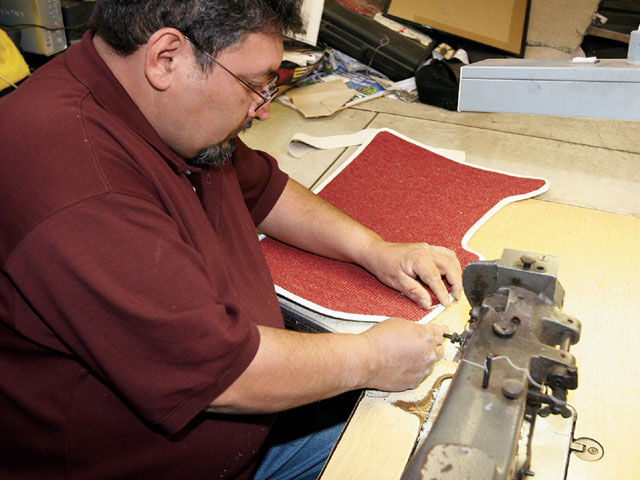 Damian sanchez of roberto's auto trim is seen here putting some lastminute touches on a carpet pad.