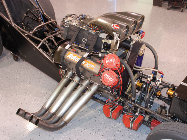 The red boxes mounted on the framerail contain the coils and amplifiers for the twin MSD magnetos. The smaller red box just ahead of them is the NHRA-mandated MSD ignition controller and rev limiter, which limits engine speeds to 8,250 rpm by retarding the ignition timing 50 degrees per second.