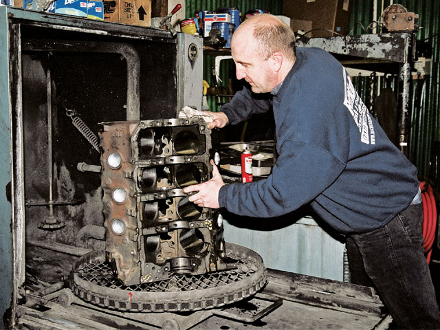 After disassembly, the engine block was thoroughly cleaned in a high-pressure spray tank. This equipment quickly removes all debris from the engine block and uses a heated detergent solution, along with pressure as high as 1,000 psi. It's similar in function to a dishwasher. Here, Rick Hartenstine loads the engine block onto the revolving turntable.