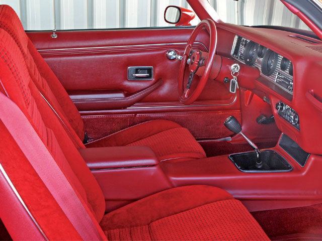 Awash in a sea of Carmine Red Lombardy velour and Mayan Red vinyl, the Trans Am's command central looks untouched from the day it left the factory.