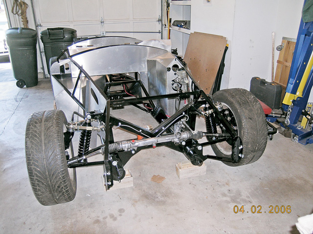 Here is a typical bare Cobra roadster chassis with the front suspension installed. The roadster kits use one of three basic layouts for front suspension: the modern Mustang (pictured), the Mustang II / Pinto layout, or the MGB/British layout from the older and original cars. By doing this, any development and engineering costs are eliminated by simply adapting an existing and proven system into the chassis rather than completely designing a new suspension and steering system. By doing this, parts can be taken directly from a donor, or affordably purchased almost anywhere.