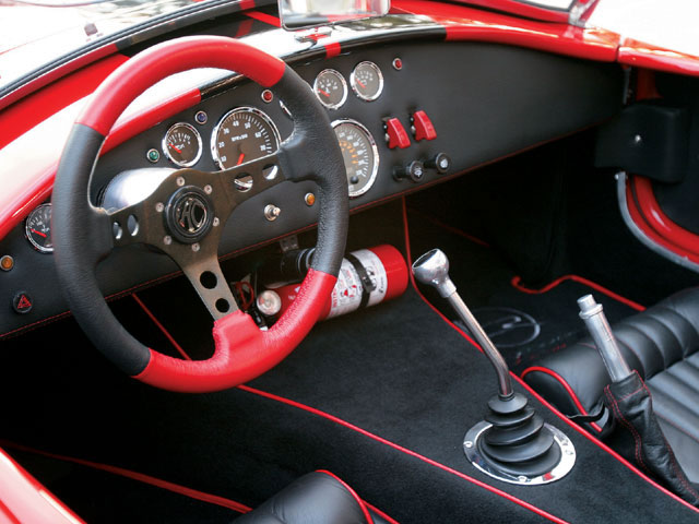 For racing, the red-and-black leather Momo steering wheel is easier to grip than the original Moto-Lita wood-rimmed wheel. The owner added a race-proven power steering pump for the rack-and-pinion steering system. VDO instruments fill the  dashboard.