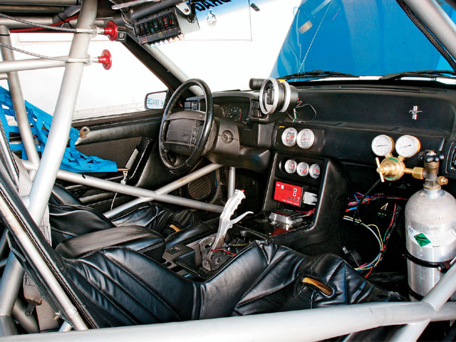 The interior is from a '90 Mustang, including the airbag (not hooked up). On the center console is the control panel for the Mallory ignition system (the red box), and the box below it activates the boost control. Data-logging is not allowed in the Street Race class. The bottle contains CO2 that controls the wastegate.