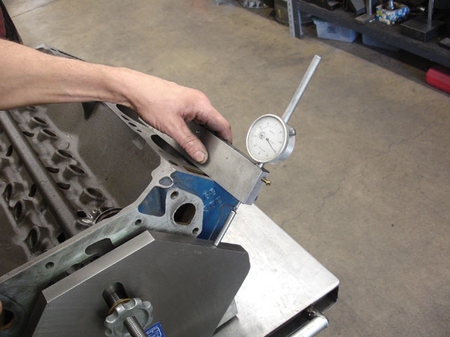 The flat bar with the dial indicator is used to determine the relative block deck heights from side to side. Running the dial indicator along the block deck will give a measurement of how far out of square the deck is with respect to the reference plate. A machinist's straightedge across the decks had shown that they were flat within a thousandth or so, but the dial indicator revealed that the decks were not the same height side to side and also out of square with the crank centerline.