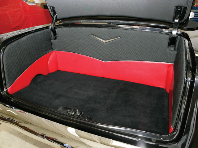 The interior's black-and-red theme is continued in the fully upholstered trunk. The latch and automatic pull-down mechanism are from an '89 Cadillac Sedan De Ville.