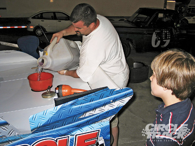 Anthony gases up #51 as a future asphalt driver looks on.