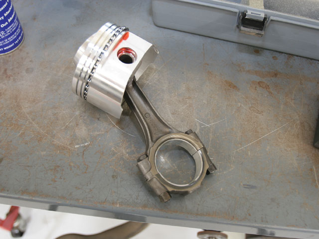 The JE/SRP pistons we found have serious domes that are designed to make 13.8:1 compression with a 58cc chamber. The pin needs to be pressed out of the rod for installation, and the pistons were nearly 80 grams lighter than the stock pistons, so we grabbed the crank and rods and took them to JMS Racing Engines to have the assembly rebalanced. Had we not balanced the assembly, the engine would have eventually eaten the bearings.