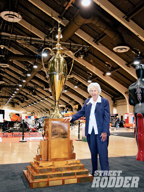 Mary Slonaker, who with her husband, Al, owned and operated the Grand National Roadster show from its inception in 1950 through the early '70s, poses alongside the huge America's Most Beautiful Roadster trophy. At 91 years, she can still recall the details and information that created the oldest custom car show in the world.