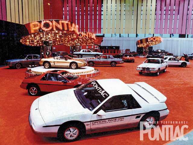 Under the guise of a mid-engine economy car, Pontiac got its Fiero into production for 1984, after which it promoted it as a mid-engine sports car. The pace car for the '84 Indianapolis 500 is shown in white, while a one-off Roadster concept car was featured on a turntable in back.
