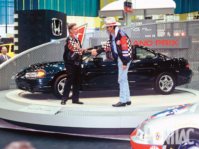 Pontiac previewed its redesigned '97 Grand Prix at the '96 Chicago Auto Show at a press conference by bringing in NASCAR team owner Richard Petty (in hat), who would field the race cars that season. Petty was introduced by Pontiac General Manager John Middlebrook. The front of his race car is lower, right.