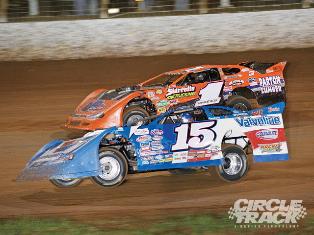 Here we see the extreme, lots of rear steer and lifting the left front wheel off the track. A four-bar Dirt Late Model rear suspension is designed to have a large range of rear steer. The adjustability allows the racer the opportunity to make adjustments for the changing conditions that occur on dirt surfaces. The attitude of the car on dry slick tracks can be quite radical.