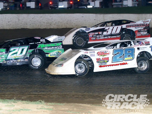 Jimmy Mars (28) works his way to the front from fifteenth starting position at Florence passing both Jimmy Owens (20) and Steve Shaver (30), both former winners of the North South 100.