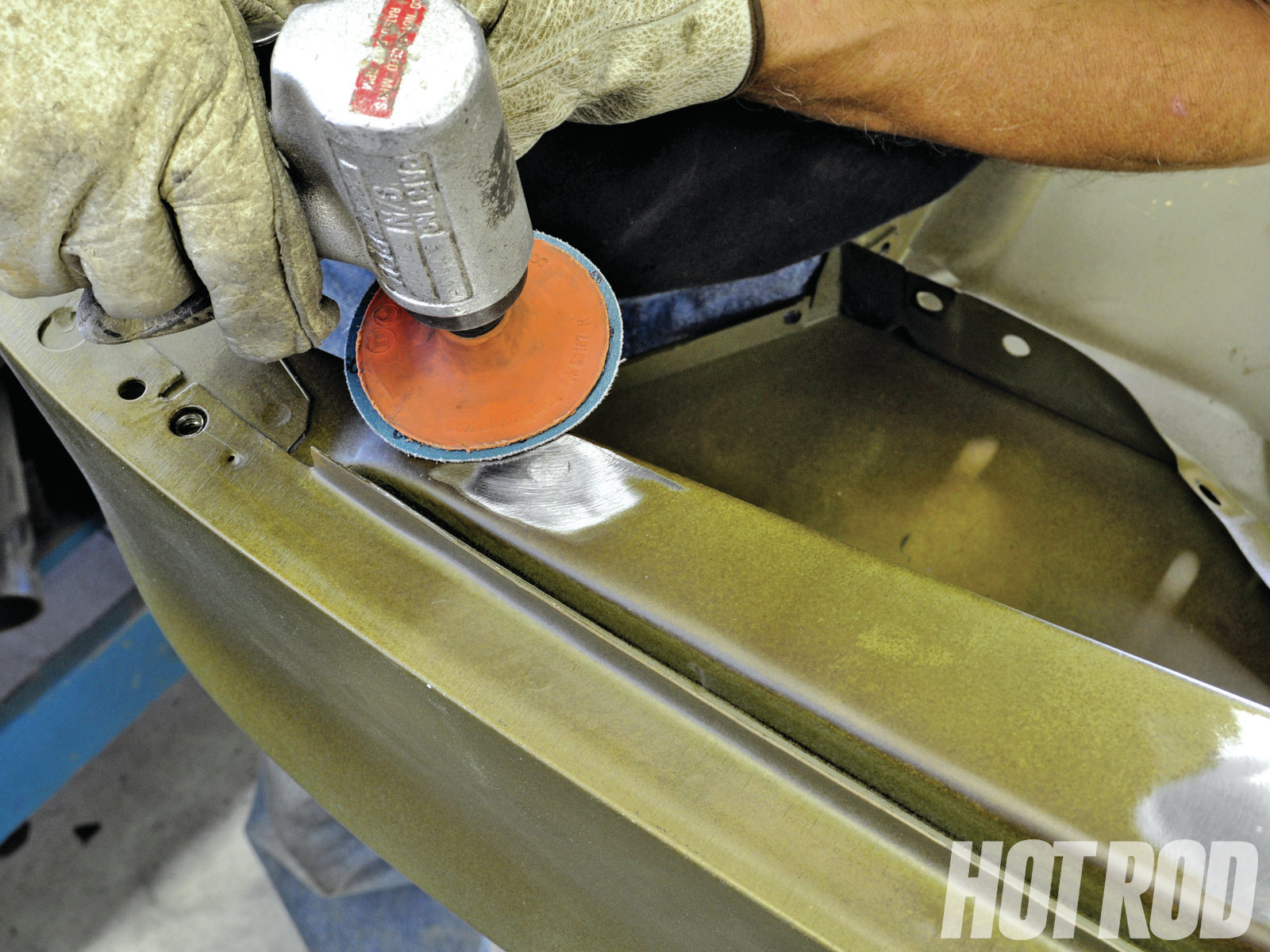 Use an abrasive disc to grind the excess metal away from the weld. Most of the time, you won't need any body filler if the weld was clean; a couple of coats of high-build primer will fill in the minor imperfections and no one will ever know there was a hole there.