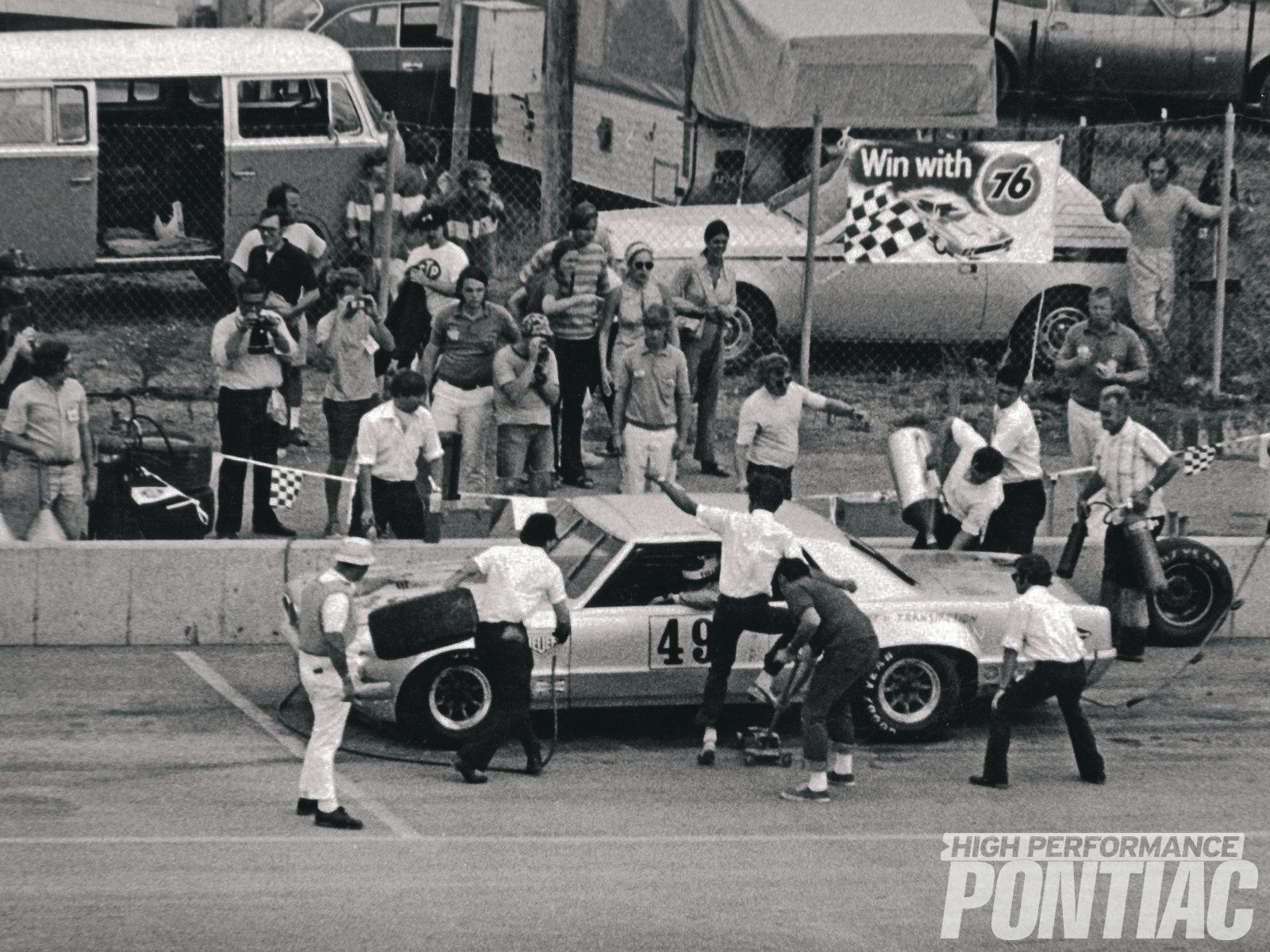 Pontiac Special Projects teammates refuel and change tires during a pit stop at the SCCA Trans-Am series race at Michigan International in 1971. The '64 LeMans is running an experimental 303 tall-deck.