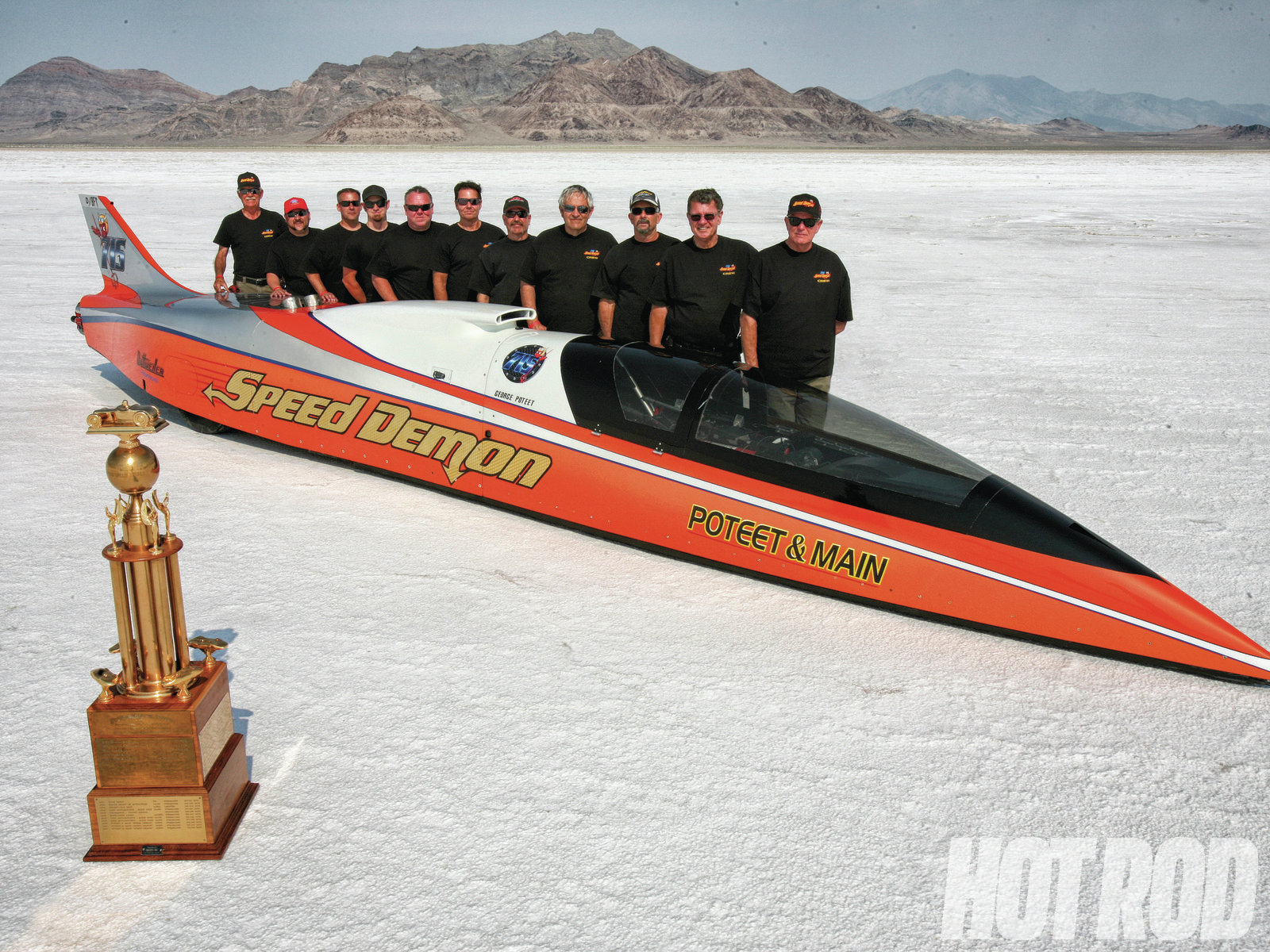 "The baddest Streamliner currently running is the Poteet & Main Speed Demon, which has taken the HOT ROD Top Time Trophy for fastest speed of the meet for four years in a row. This year's incredible flying mile speed, with George Poteet driving, was 423.325 mph, the biggest number seen on the trophy in 11 years (though the car has done 462 at the '11 FIA meet). Only Streamliner and Unlimited Diesel Truck are allowed to run multiple engines, but Speed Demon has been getting it done with single small-block V8s turbocharged by Kenny Duttweiler. An overview of the car's 347ci, 2,000hp engine is in the story ""Demonic"" in the Apr. '12 HRM. This year, the D-class engine was just 300 ci. The crew, seen here from left to right, is Nate Jones, Ian Mann, Greg Pyles, Aron Cranford, Steve Watt, David Main, David Diviak, Kenny Duttweiler, Joe Galati, Ron Main, and George Poteet."