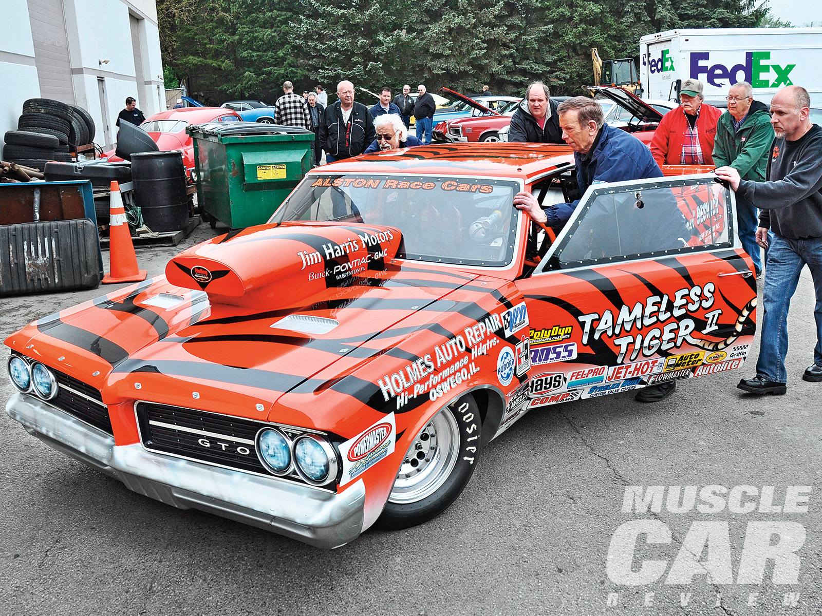 "Drag racing legend Arnie ""the Farmer"" Beswick was at the show with his '64 GTO Tameless Tiger II representing Holmes Auto Repair in Oswego, Illinois. Arnie was leading the crew to push his race car into position and was promptly greeted with a surprise gathering for his 82nd birthday. When is the last time you saw an 82-year-old gentleman pushing the race car he still drives at speeds of more than 170 mph?"