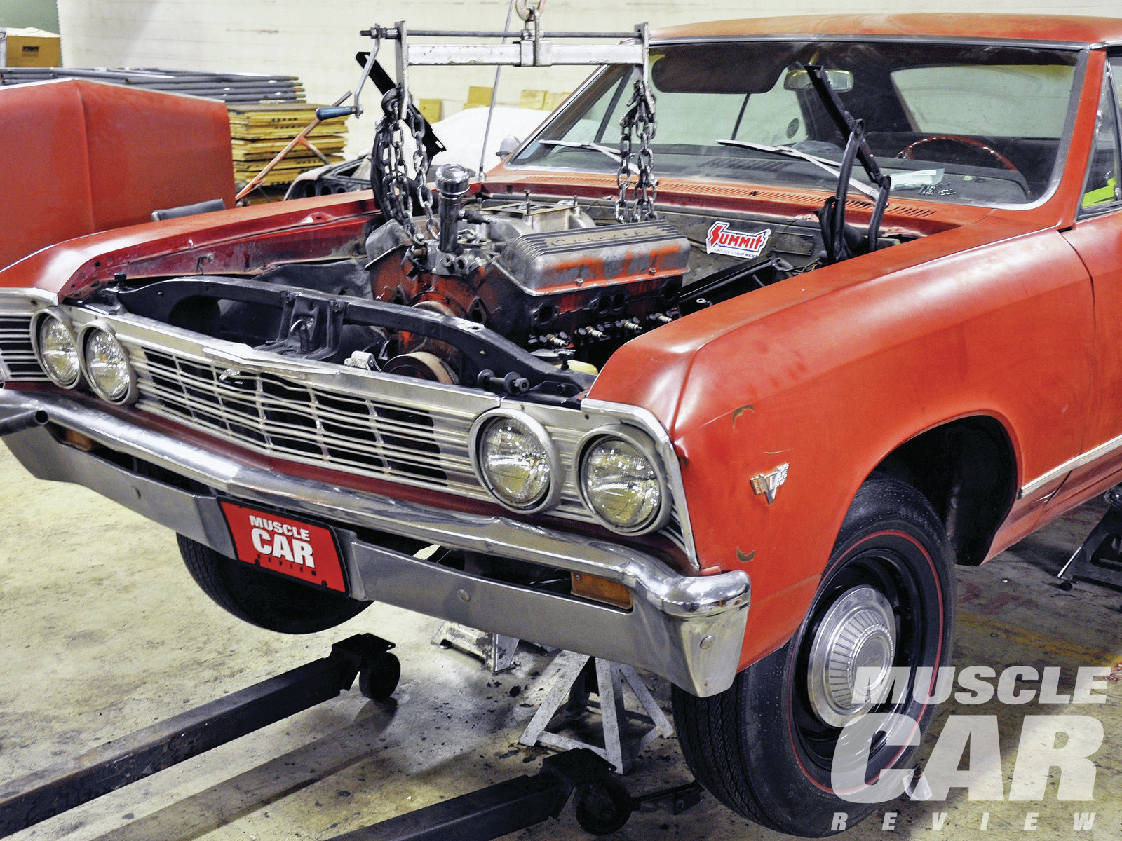 The 327 is lowered into the engine compartment, carefully avoiding contact with the radiator support, the firewall, or the wheelwells. Frankly, the small-block engine provides plenty of margin for error during installation, since the Malibu's engine bay was designed to swallow much bigger motors.
