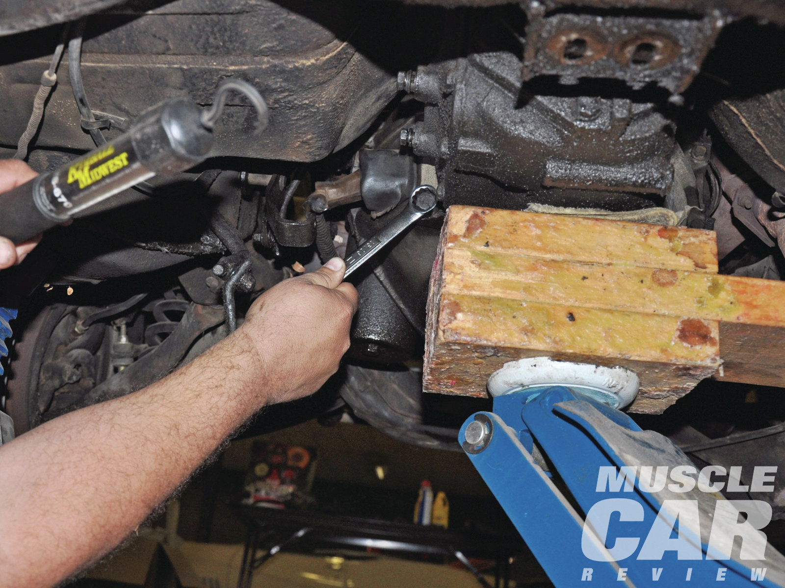 Take out the bolts from the transmission mount on the transmission crossmember. A floor jack with a block of wood supports the manual transmission while you remove the four bolts. Once the bolts are gone, have a buddy lower the jack while you slowly pull the transmission out.