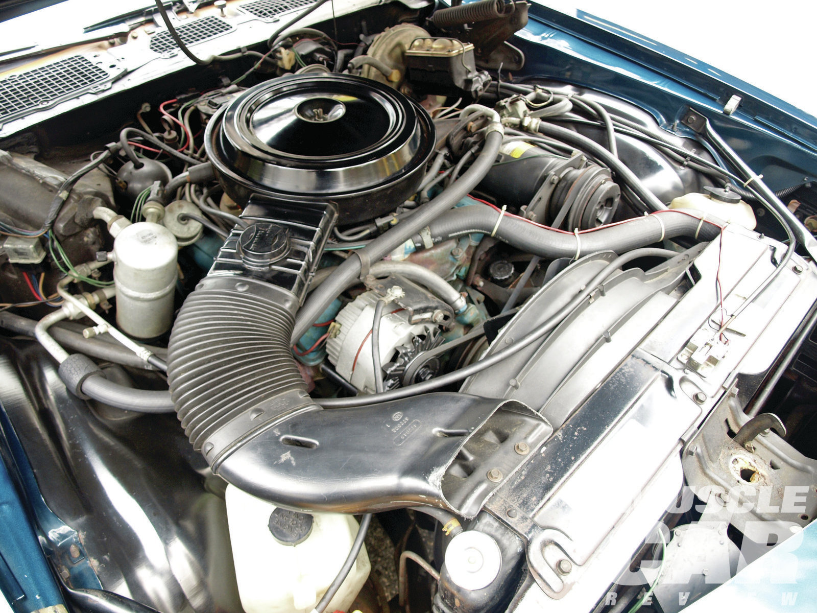 The bland presentation of the engine is a product of its time. The EPA had Detroit running scared -- performance was a dirty word -- so engineers had to be subtle. Still, the LM1's Rochester Quadrajet spread-bore carburetor did a great job of combining low-speed response, top-end breathing, and reasonable fuel economy. Note the round diaphragm and lever that are part of the optional K30 Cruisemaster cruise control, a $103 option.