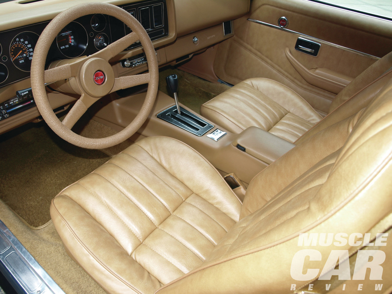 The camel-color vinyl interior and matching carpets are original and unrestored. About 75 percent of all '79 Z28s came with the TH350 automatic seen here; the rest were ordered with the close-ratio BorgWarner T10 four-speed (which wasn't available in California). The control switches for the optional A31 power windows are located atop the center console. About one in three Camaro buyers paid the extra $132 for power windows. Note the (rare) cruise control button integrated into the turn-signal stalk.