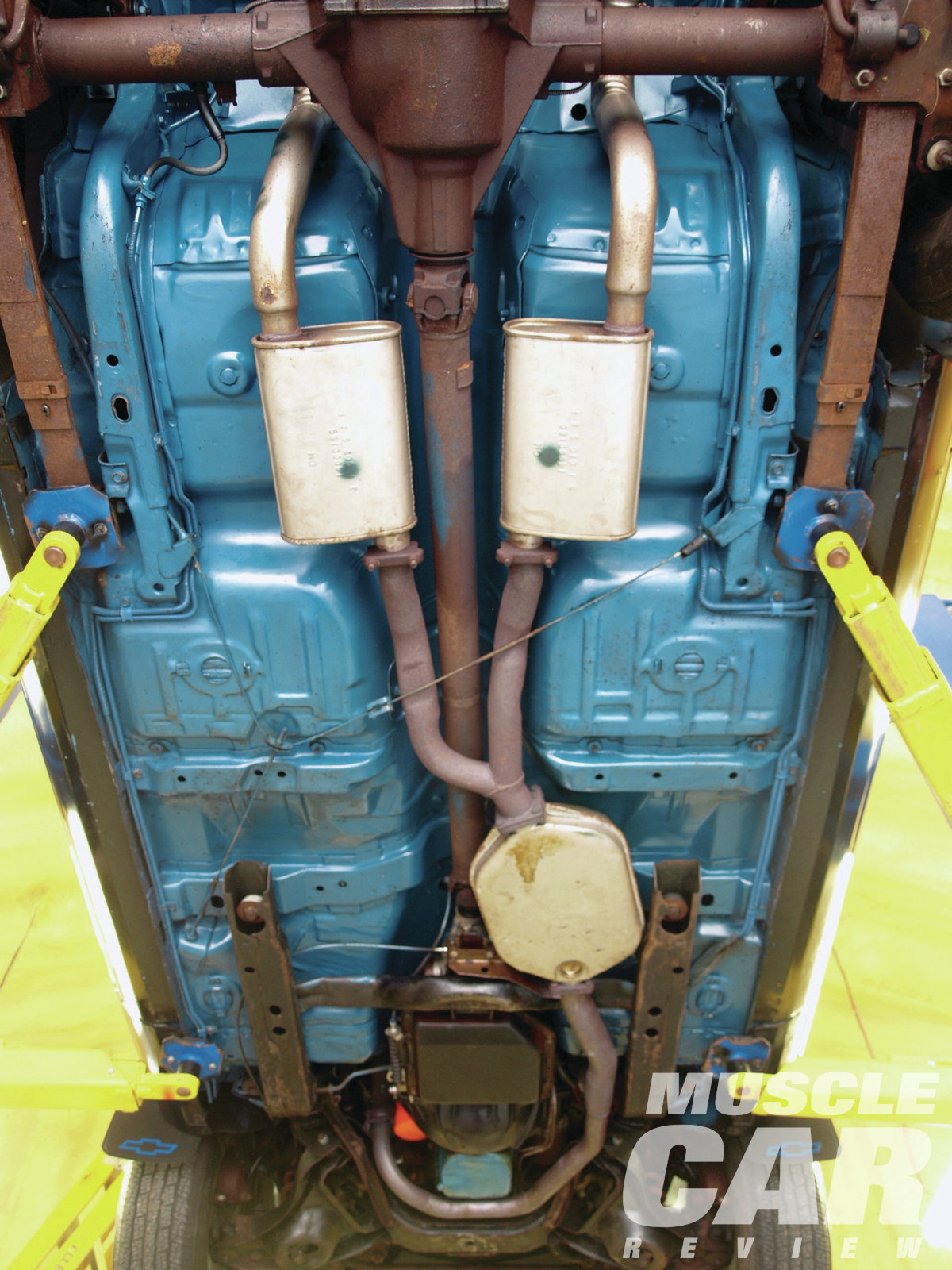 Here's a view of the paint the original owner applied to the undercarriage. Note how GM cut costs by routing the dual head pipes into a single pellet-bed-style catalytic converter. Notice, too, how the factory welded the mufflers to the tailpipes. Correctly restored, these need to be presented as one-piece assemblies.