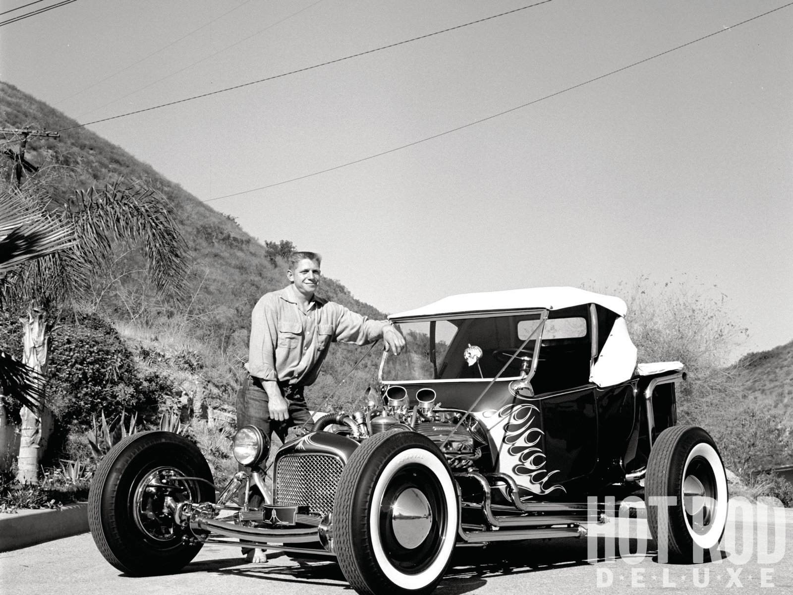"""These two shots turned up on a roll exposed by Bob D'Olivo for Car Craft in late November 1956, depicting the roadster as most folks remember it from television appearances. In the year and a half since HRM's initial photo session, Norm obviously made many modifications. The custom ragtop was inspired by a stunt driver's crash. Norm rightly reasoned that by concealing the driver from most camera angles, he could hire himself out for film and TV gigs, along with the vehicle. The identity of the beer-chugging child remains a mystery, as Grabowski never fathered any, according to old friends. Even the photographer draws a blank: """"The kid can't possibly be related,"""" quipped D'Olivo. """"He's wearing shoes, and Norm isn't!"""""""