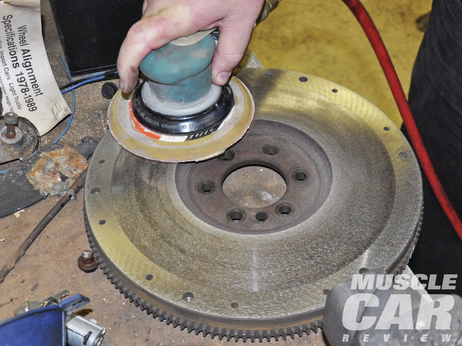 The flywheel should be resurfaced at the local machine shop. However, since the flywheel showed signs of a recent resurfacing, Webster decided that a DA with 40-grit paper would prepare the surface sufficiently.