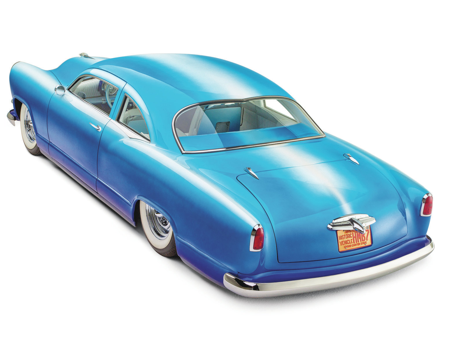 Winfield's blue fade paint continues into the interior of the Kaiser and is visible through the heart-shaped rear window. That window shape is a stock Kaiser design element, and Keith scored an N.O.S. piece of glass for his car. Because he didn't want to risk breaking it, the window is sunk down and tilted forward rather than cut to match the chopped top.