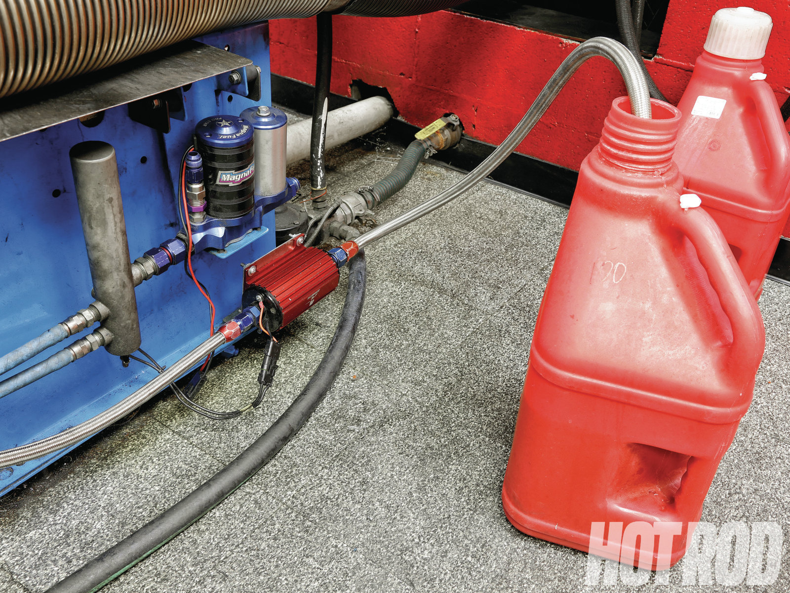 [11] Although every test cell is set up differently, the fuel system in SAM's dyno room is as simple as it gets. Two pumps—one for EFI and another for carbureted setups—are mounted to the dyno frame and draw fuel directly from 5-gallon jugs. From there, two short feed lines run forward from each pump to the top of the motor. Switching from an EFI to carbureted fuel system is as easy as swapping feed lines.