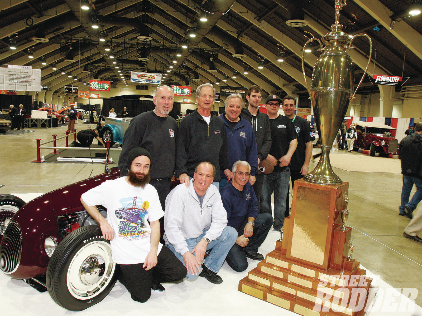 The building of an award-winning car is seldom an individual effort. Mumford (closest to the AMBR trophy) is flanked by Brizio and shop staff. One of the industry's premier painters is Darryl Hollenbeck (second from left) of Vintage Color Studio, who receives a big attaboy for the flawless paintwork. (Photo by Tim Bernsau)