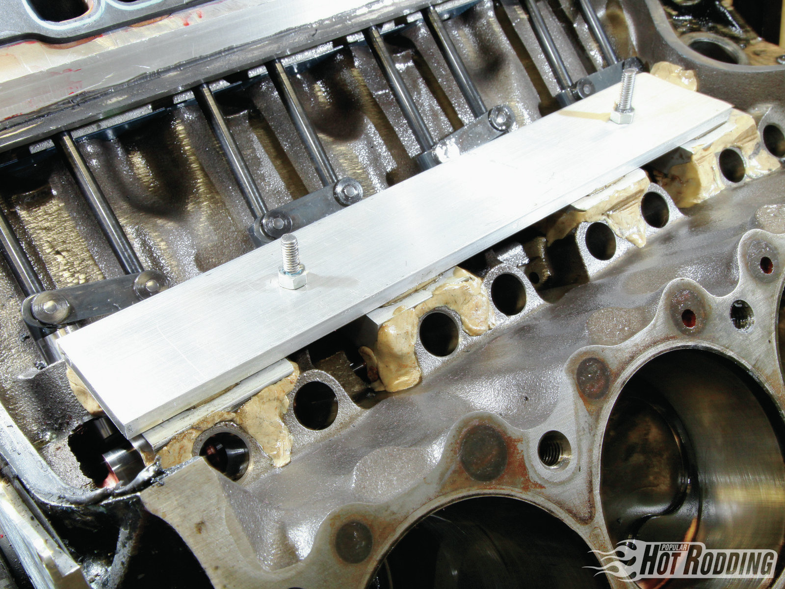 With the open lifter bores of a Pontiac block, side loading from a roller cam can induce stresses that can potentially result in breakage. Semchee buttressed this area with custom aluminum supports bedded in epoxy.