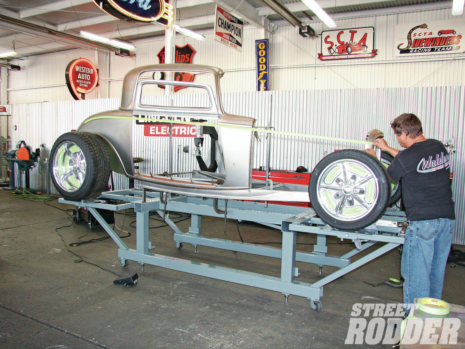 The side panel is placed on his jig, and tape is used to eyeball where the coupe's body line will be, plus the height of the grille and radiator. (Note the rear wheel is placed just for general reference).