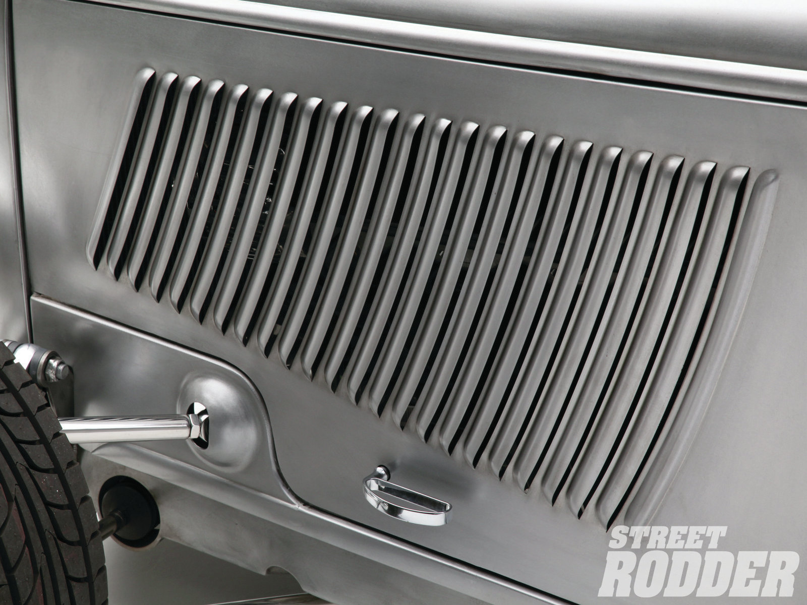 19| Walden ordered an oversize piece of metal stamped with '33 Ford louvers from Rootlieb, then cut and shaped them to fit Warren's car. Check out the cool blister made for the upper control arm.