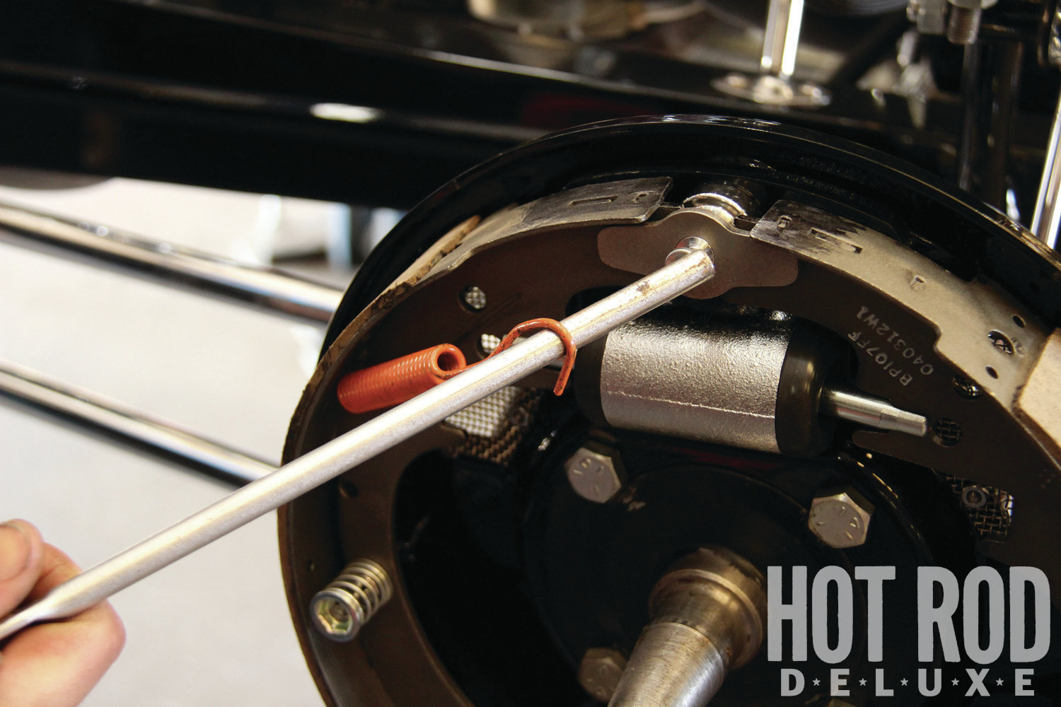 [12] Install the brake springs onto the anchor pin, using the notched end of brake-spring pliers for leverage. This takes a little elbow grease.