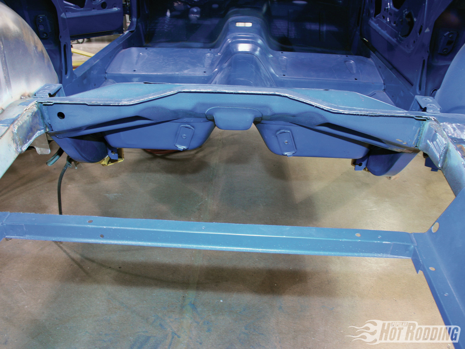 4. Once the rear cutline has been established, begin cutting from the center of the floorpan out toward the framerails on each side using a cutoff wheel. The front flange line of the trunk pan is clearly visible from beneath the car, which serves perfectly as the front cutline. Next, cut the sides of the trunk floor as close to the framerails as possible, then remove the entire pan.