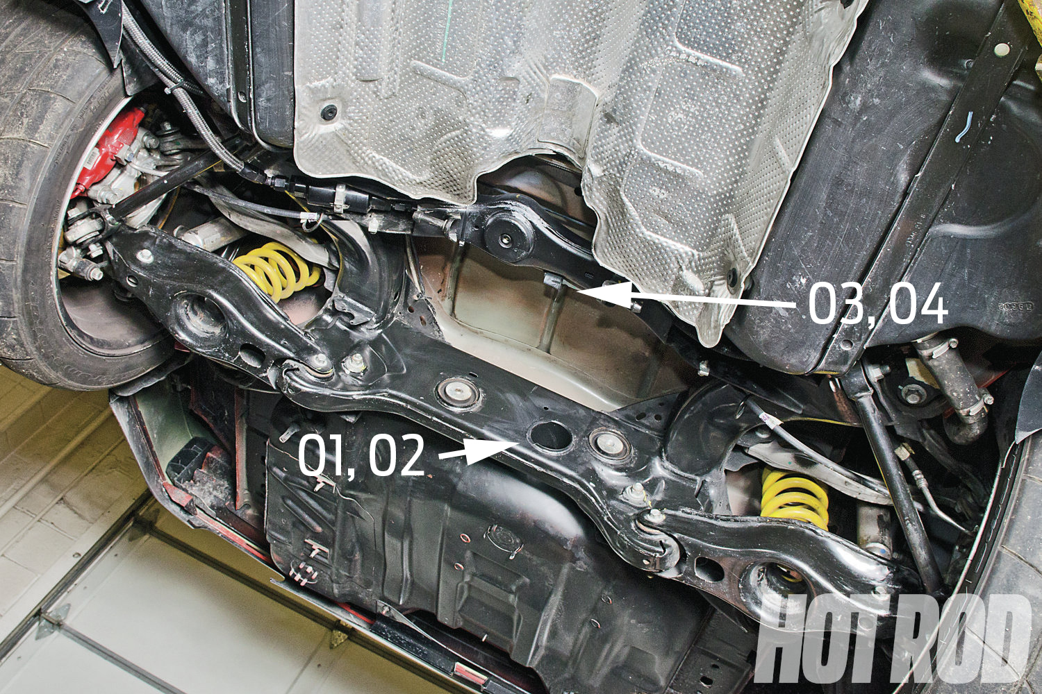 To get the Pro60-IRS to fit in the car, the flanged through-hole's lip on the IRS's rear cradle crossover was trimmed (details, photos 01–02). On the forward horizontal crossover, the double-walled member was messaged near the forward housing mount (photos 03–04).