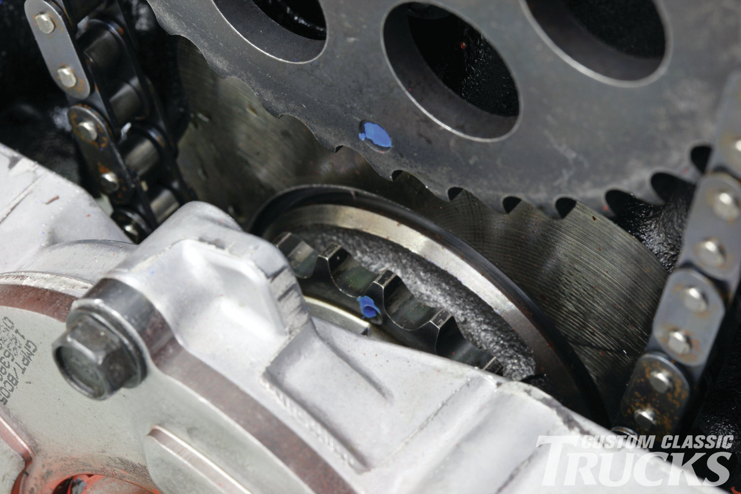 6. Before removing the top timing gear, make sure that you rotate the motor and align the dots on the top and bottom gears. This will ensure proper cam timing when the new one is installed. The blue dots are factory paint marks.