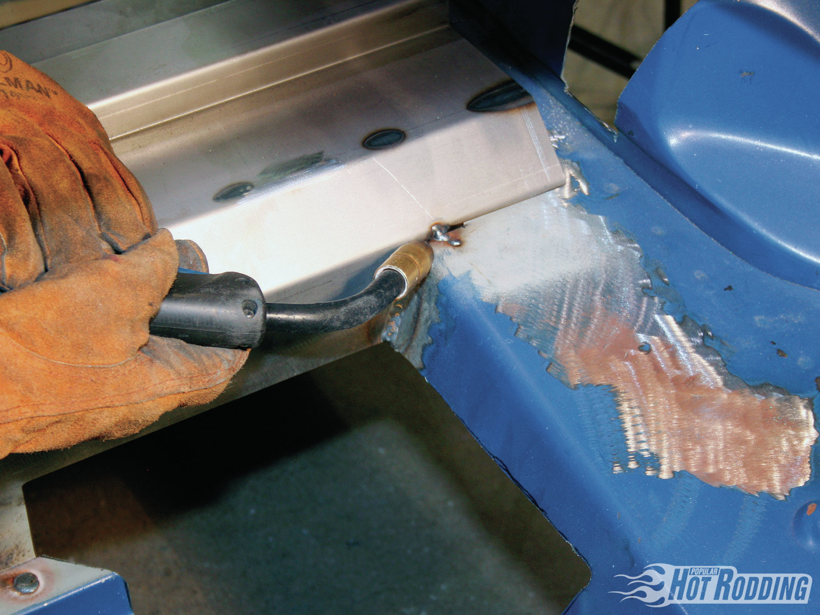 7. With the plug welding complete, seam weld the sides of the new trunk pan to the body. Remember to grind paint off the body to bare metal before welding, and apply a coat of weld-thru primer along the joints to prevent rust.