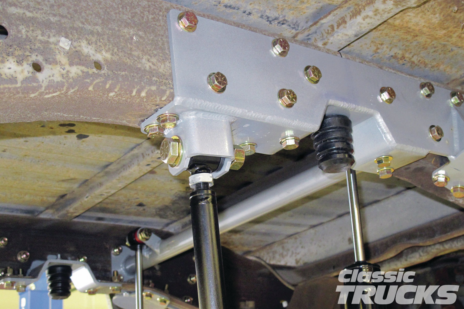 9. With the holes drilled on both sides, the next step was to install the upper shock crossbar from one end to the other. It is also a good time to install the soft rubber bumpstops for the rearend. The bar hanging down on the left is the Panhard bar; this will mount on the rearend via a welded on bracket.